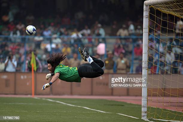 Former Colombian goolkeeper Rene Higuita kicks the ball to save a goal during an exhibition match between the Brazilian Masters and Indian All Stars...