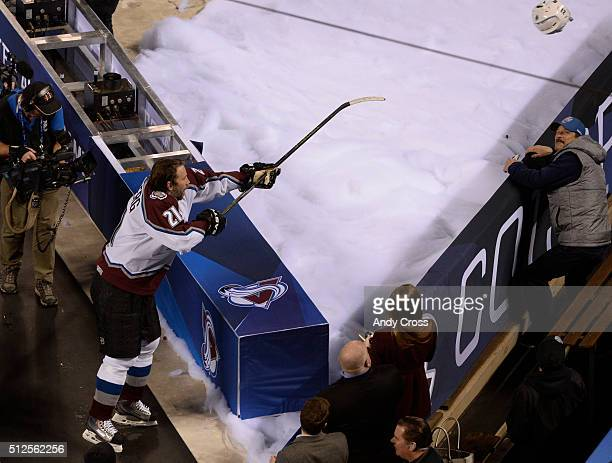 Former Colorado Avalanche center slings his helmet to a luck fan after defeating the Detroit Redwings at the NHL Stadium Series Alumni game at Coors...