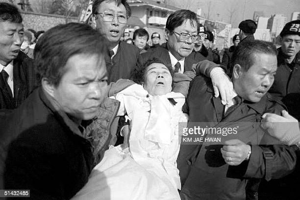A former comfort woman who fainted while taking part in a demonstration near the Japanese Embassy 09 February 1993 is carried away from the scene as...