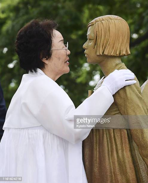 """Former """"comfort women"""" touches on Aug. 14 a memorial statue in Seoul symbolizing women like her, forced to work in the Japanese military's wartime..."""