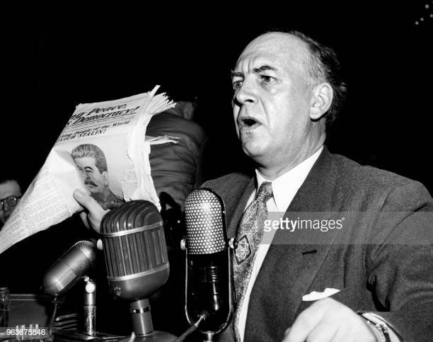US former communist activist and writer Louis F Budenz holds a copy of a newspaper as he testifies before Senate Foreign Relations Subcommittee...