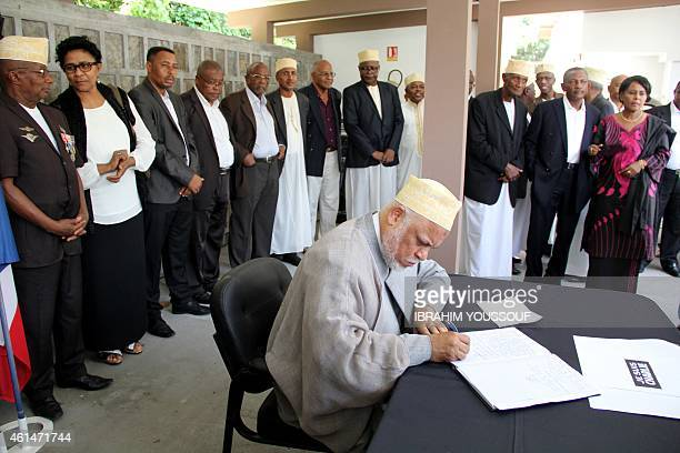Former Comoros president Ahmed Abdallah Sambi signs a condolences book during a memorial service for the people killed during the attacks on the...