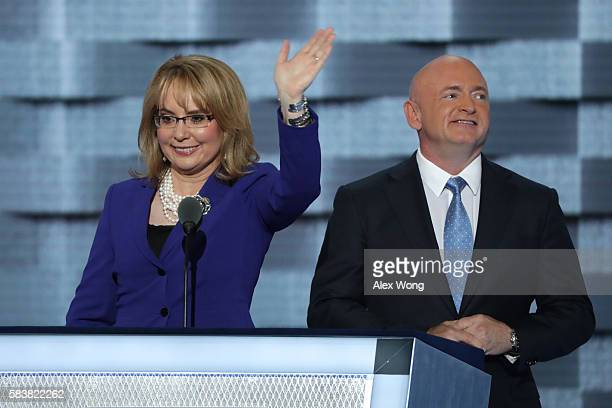 Former Congresswoman Gabby Giffords waves to the crowd as her husband, retired NASA Astronaut and Navy Captain Mark Kelly, looks on after delivering...