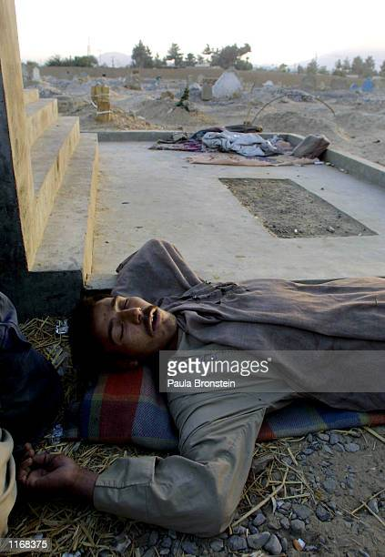 Former cook from Afghanistan, now a homeless drug addict, lies next to a tomb after injecting heroin at a cemetary October 17, 2001 in Quetta,...