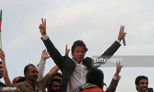 Former cricketer and chairman of Pakistan's political party Pakistan Tehreek-e-Insaf, Imran Khan, gestures during a public meeting in Lahore on March...