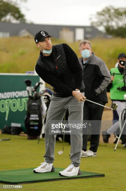 Former Cricketer Freddie Flintoff plays a shot as TV presenter Piers Morgan looks on as they take part in the Paddypower Pro-Am Golf Shootout on June...
