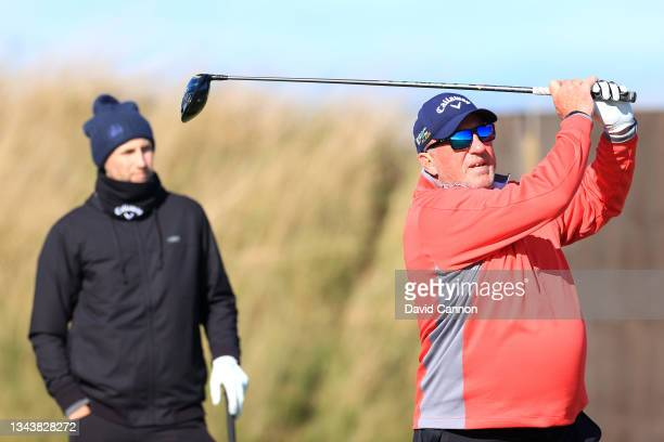 Former cricketer Ian Botham plays a shot as Joe Root looks on during a practice round ahead of The Alfred Dunhill Links Championship at Kingsbarns on...