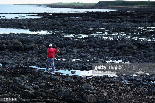 Former cricketer Sir Ian Botham plays his second shot on the 15th hole from the rocks during the third round of The Alfred Dunhill Links Championship...