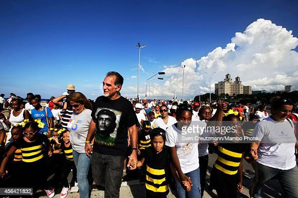 Former Cuban agent Rene Gonzalez wears a Che Guevra Tshirt as he and his wife Olga Salanueva and Cuban students numbering reportedly in the thousands...
