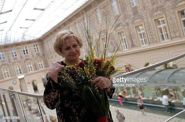 Former Czech gymnast Vera Caslavska poses with a bouquet after holding a press conference on May 2 2012 in Prague Caslavska one of the most titled...