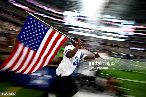 Former Dallas Cowboys player George Teague carries the American flag onto the field prior to the game between the Dallas Cowboys and New York Giants...