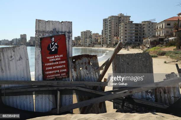 "Former, decaying hotel buildings stand beyond a makeshift barrier and a Turkish military sign inside the ""Forbidden Zone"" of Varosha district on..."