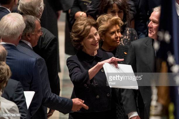 Former Defense Secretary Leon Panetta left greets former President George Bush right as he and his wife former first lady Laura Bush follow the...