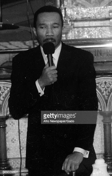 Former Democratic Congressman from Maryland Kweisi Mfume wearing a suit and holding a microphone 1991