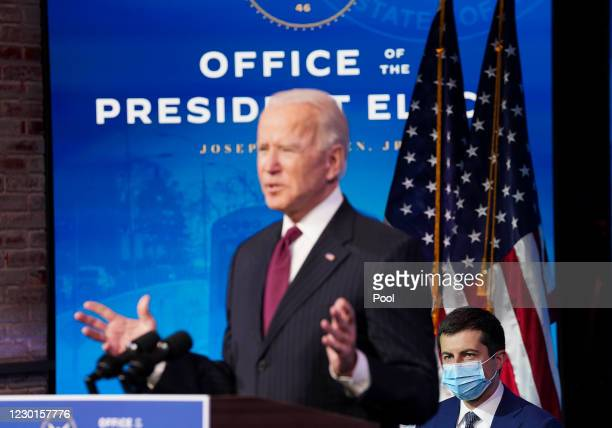 Former Democratic presidential candidate Pete Buttigieg listens as U.S. President-elect Joe Biden announces his nomination during a news conference...