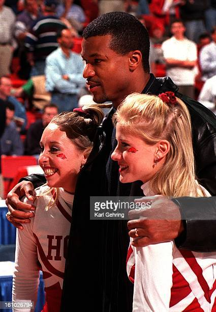 Former Denver Bronco safety Steve Atwater posed for pictures with University of Arkansas cheerleaders Jana Byrd left and Melissa Neeley right during...
