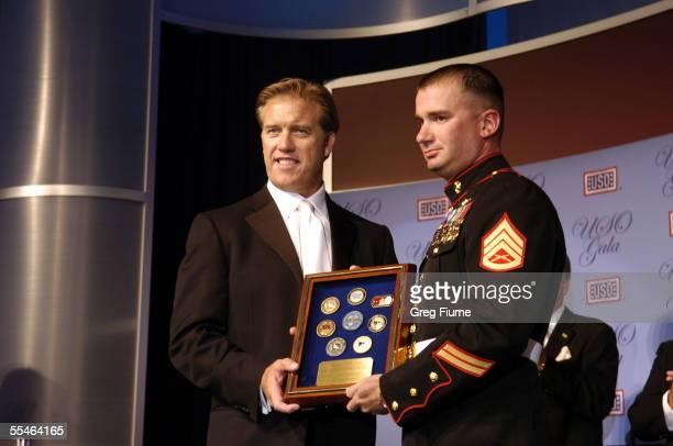 Former Denver Broncos quarterback John Elway presents the U.S. Marine Corps award to Staff Sergeant Matthew T. Anderson at the USO Gala honoring...