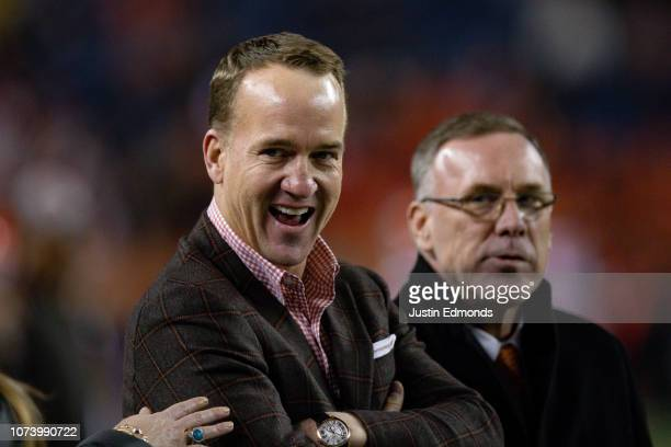 Former Denver Broncos quarterback Peyton Manning stands on the field before a game between the Denver Broncos and the Cleveland Browns at Broncos...