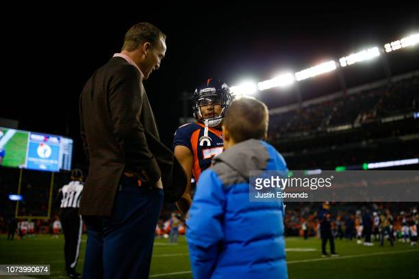 Former Denver Broncos quarterback Peyton Manning stands on the sideline with his son and running back Phillip Lindsay before a game against the...