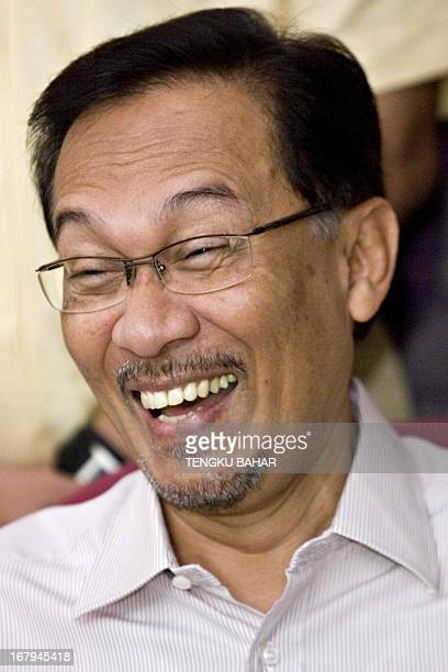 Former deputy prime minister and de facto opposition leader Anwar Ibrahim reacts to a lighthearted comment during a press conference in Kuala Lumpur...