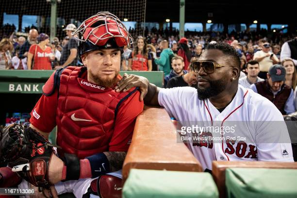 Former designated hitter David Ortiz of the Boston Red Sox talks with Christian Vazquez of the Boston Red Sox after throwing out a ceremonial first...