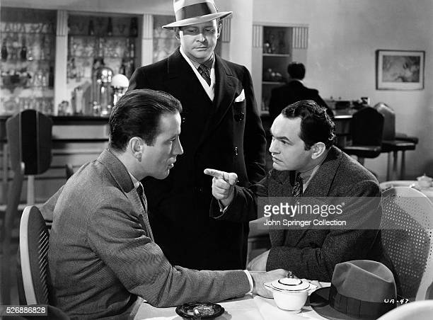 Former detective Johnny Blake sternly points at Lee Morgan in a scene from the 1936 film Bullets or Ballots
