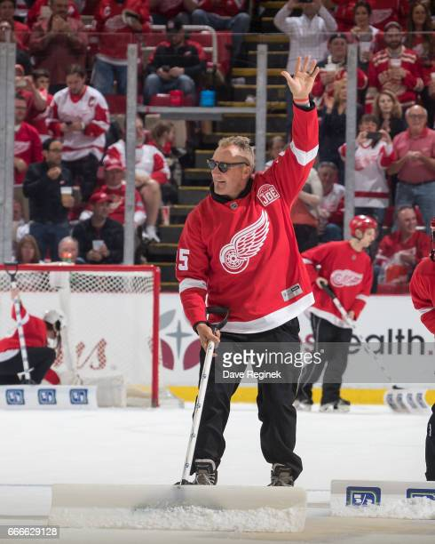 Former Detroit Red Wing Darren McCarty waves to the crowd as he shovels the ice during a stoppage of play in an NHL game against the New Jersey...