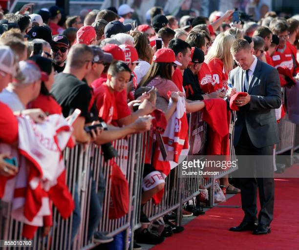 Former Detroit Red Wing Kris Draper autographs a hat as he walks the red carpet after arriving at Little Caesars Arena for the Red Wings game against...
