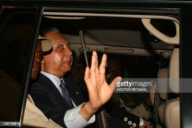 Former dictator JeanClaude Baby Doc Duvalier waves from his limousine after making a surprise return to Haiti on Sunday January 16 in the midst of a...