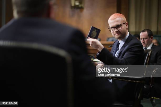Former director of research for Cambridge Analytica Christopher Wylie pulls out his Canadian passport before testifying to the Senate Judiciary...
