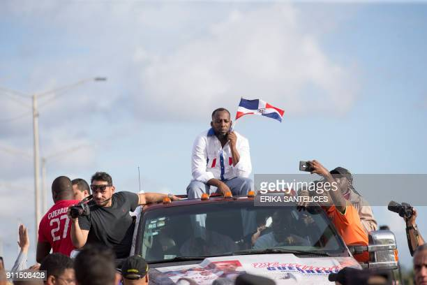 Former Dominican Major League baseball player Vladimir Guerrero holds a Dominican flag as he is driven through the streets after arriving at the Las...