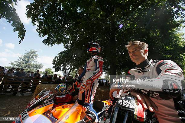 Former double World Moto GP Champion Casey Stoner stands on his Honda while waiting to ride up the hill with Superbike riders Chaz Davies and Leon...