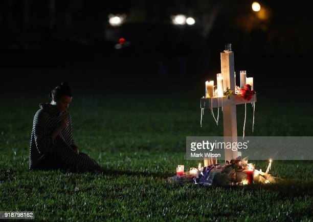 Former Douglas student Rachelle Borges sits near a candlelit cross during a vigil for victims of the mass shooting at Marjory Stoneman Douglas High...