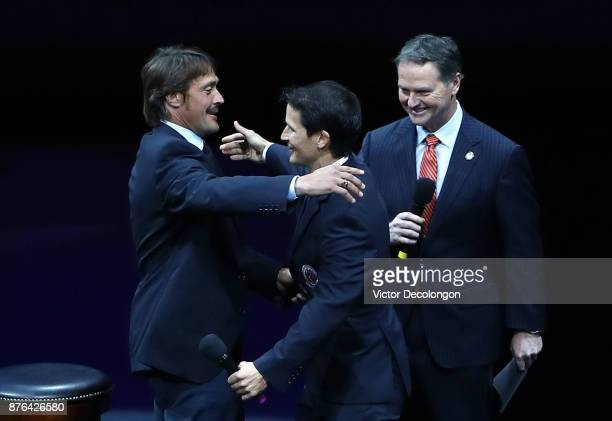 Former Ducks players Teemu Selanne and Paul Kariya hug after being introduced at center ice byt Ducks commentator Brian Hayward prior to discussing...