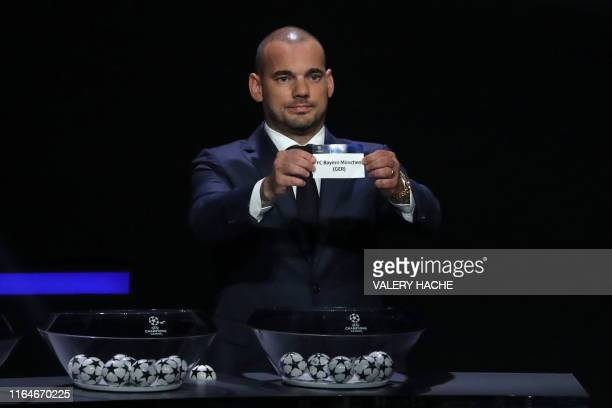 Former Dutch international Wesley Sneijder holds the slip of FC Bayern Munich during the UEFA Champions League football group stage draw ceremony in...