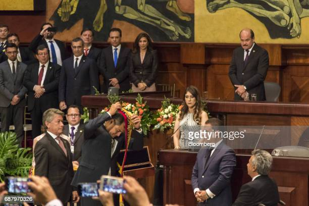 Former Ecuadorian president Rafael Correa center left removes the presidential sash as Lenin Moreno Ecuador's presidentelect right watches during the...