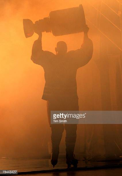 Former Edmonton Oilers great Mark Messier is silhouetted as he hoists the Stanley Cup while skating onto the ice during a ceremony to raise his...