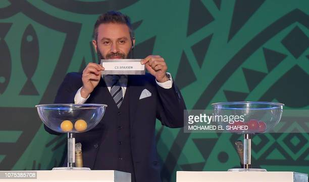 Former Egyptian player Hazem Mohammed Abdehamid Emam shows the results during the draw of the Confederation of African Football's Confederation cup...