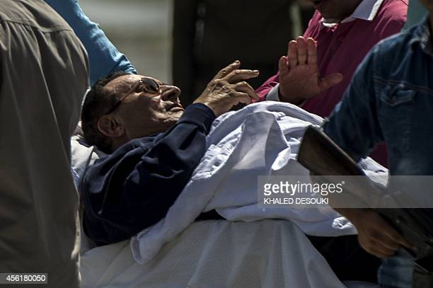 Former Egyptian president Hosni Mubarak is wheeled out of a helicopter into an ambulance outside the Maadi military hospital in Cairo on September...