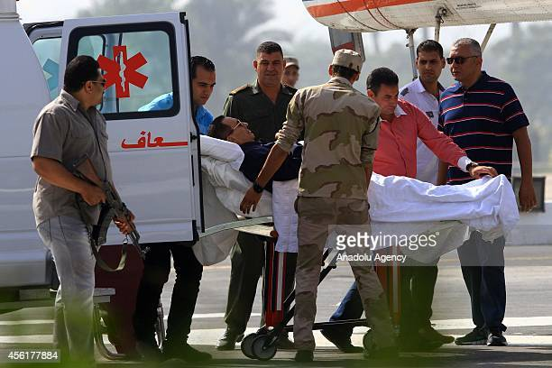 Former Egyptian president Hosni Mubarak is wheeled out of an ambulance outside the Maadi military hospital in Cairo on September 27 2014 before...