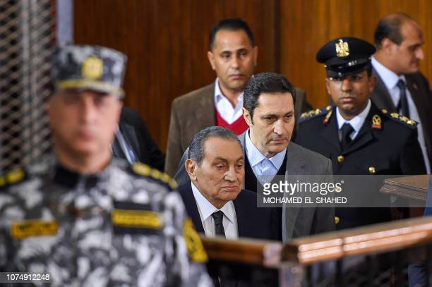 Former Egyptian president Hosni Mubarak , who was ousted following a popular uprisal in 2011, arrives with his sons Alaa to testify during a session...