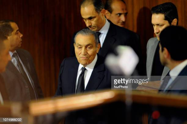Former Egyptian president Hosni Mubarak who was ousted following a popular uprisal in 2011 is escorted by his two sons Alaa and Gamal as he testifies...