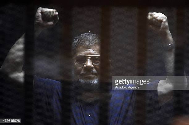 Former Egyptian President Mohamed Morsi gestures as he stands inside the defendants' cage in a courtroom during his trial in Cairo Egypt on June 02...