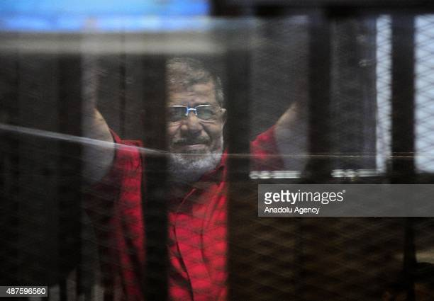 Former Egyptian President Mohamed Morsi gestures as he stands inside the defendants' cage in a courtroom at the police academy during his trial over...