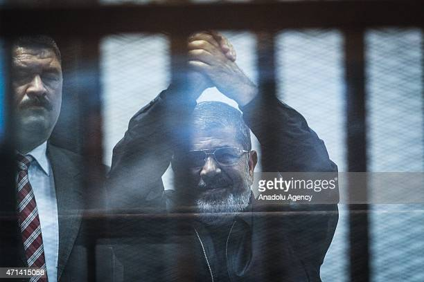 Former Egyptian President Mohamed Morsi in blue clothes stands inside a glass defendant's cage during the hearing in police academy in Cairo Egypt on...
