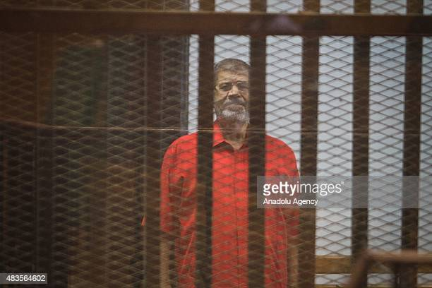 Former Egyptian President Mohamed Morsi stands inside the defendants' cage in a courtroom at the police academy during his trial over espionage with...