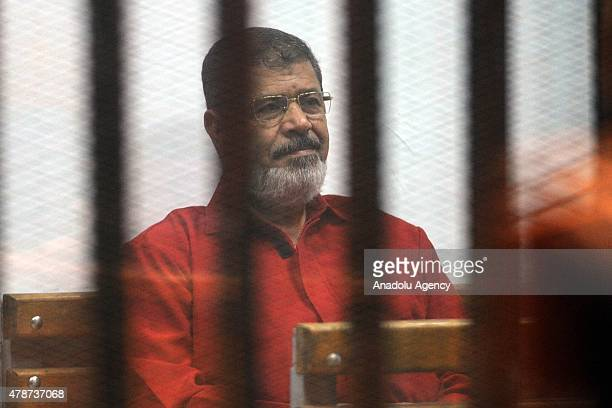 Former Egyptian President Mohamed Morsi, wearing a red uniform after Cairo Criminal Court sentenced him to death over a prison break in 2011, stands...