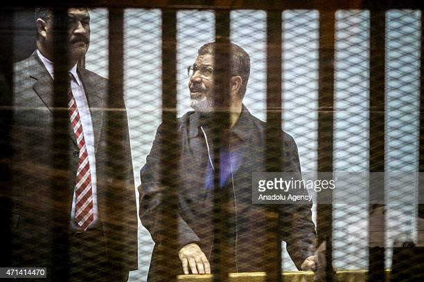 Former Egyptian President Mohamed Morsi wearing blue clothes stands inside a glass defendant's cage during the hearing in police academy in Cairo...