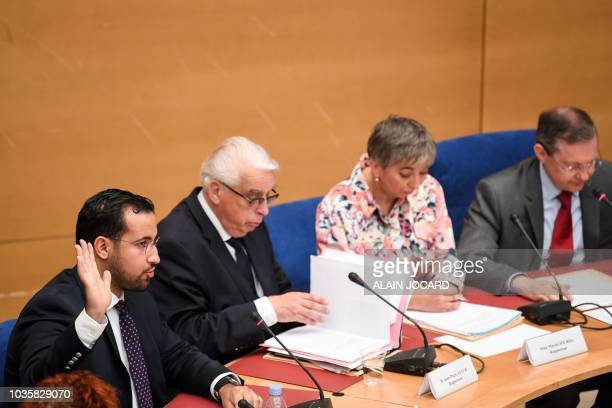 Former Elysee senior security officer Alexandre Benalla raises his hand as he takes the oath before a Senate committee as he sits next to rapporteur...
