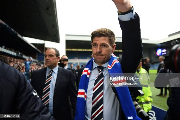 Former England and Liverpool captain Steven Gerrard gestures as he is introduced to supporters inside Ibrox stadium after being unveiled as Rangers'...